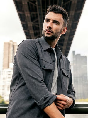 model wearing men's charcoal tweed fusion overshirt and pale grey heather composite merino tee standing outside under a bridge rolling up sleeves