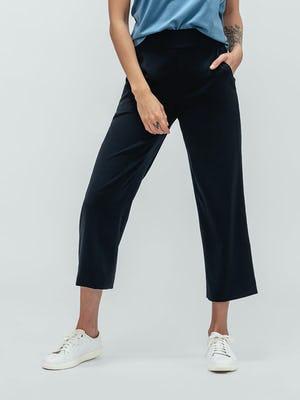 Woman with curly hair wearing blue composite merino tank top and navy swift drape pants with sneakers