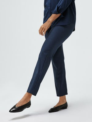 women's navy juno blouse and azurite heather velocity pant model facing forward extending leg sleeve cuffed