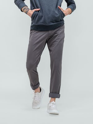model wearing dark charcoal fusion terry sweatshirt and medium grey pace tapered chino facing forward with pant legs cuffed and hands in kangaroo pocket