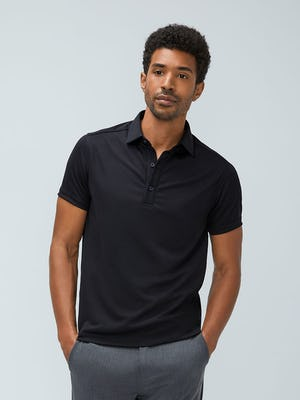Men's Black Apollo Polo and Men's Graphite Velocity Pant on Model walking forward with hands in pants pockets