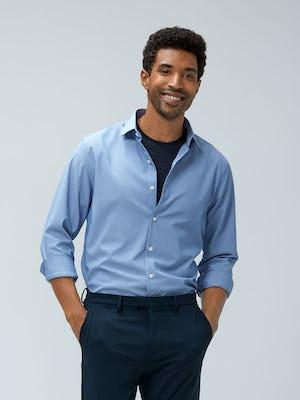 Men's Blue Oxford Aero Zero Dress Shirt and Men's Dark Navy Velocity Pant on model walking forward with hands in pants pockets
