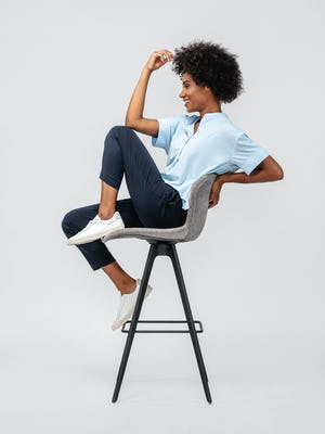 Navy Women's Swift Drape Pant and Chambray blue Juno Boxy Blouse on model sitting in chair with legs up