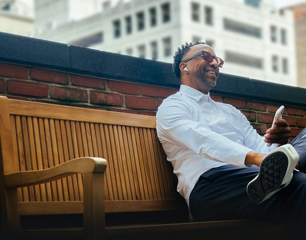 man sitting on a bench using his phone wearing a white aero zero dress shirt