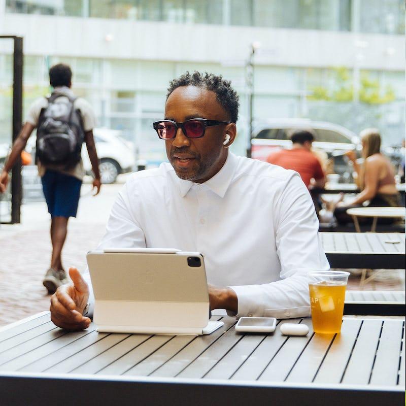 man sitting outdoors using a tablet wearing a white aero zero dress shirt