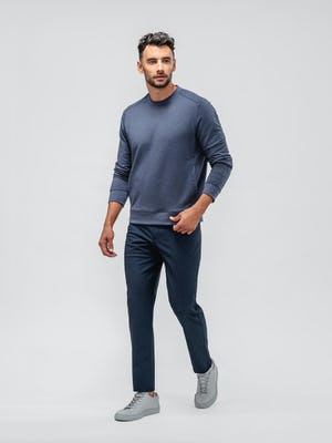 model wearing steel blue heather kinetic twill 5 pocket pant and navy fusion terry sweatshirt facing forward with sleeves pulled up