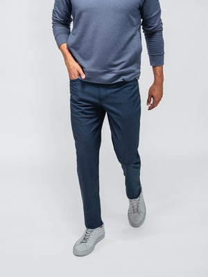 model wearing steel blue heather kinetic twill 5 pocket pant and navy fusion terry sweatshirt facing forward with hand in pocket