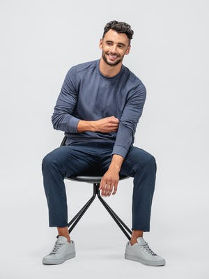 model wearing steel blue heather kinetic twill 5 pocket pant and navy fusion terry sweatshirt sitting on a stool with sleeves pulled up