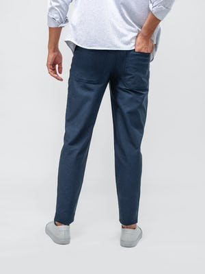 model wearing steel blue heather kinetic twill 5 pocket pant and blue stripe hybrid button down facing away with hand in back pocket