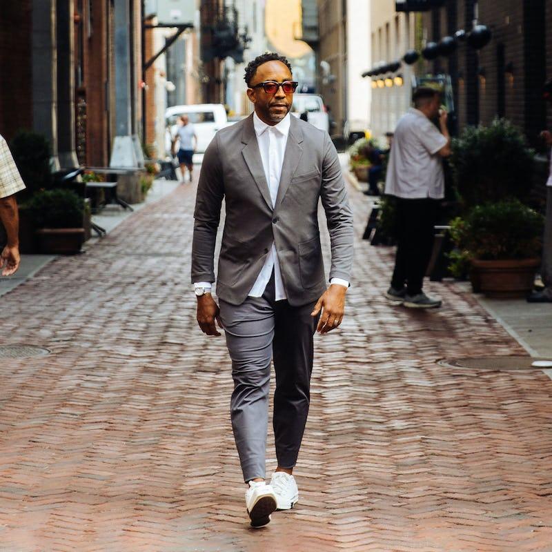 man walking down the street wearing a grey kinetic suit