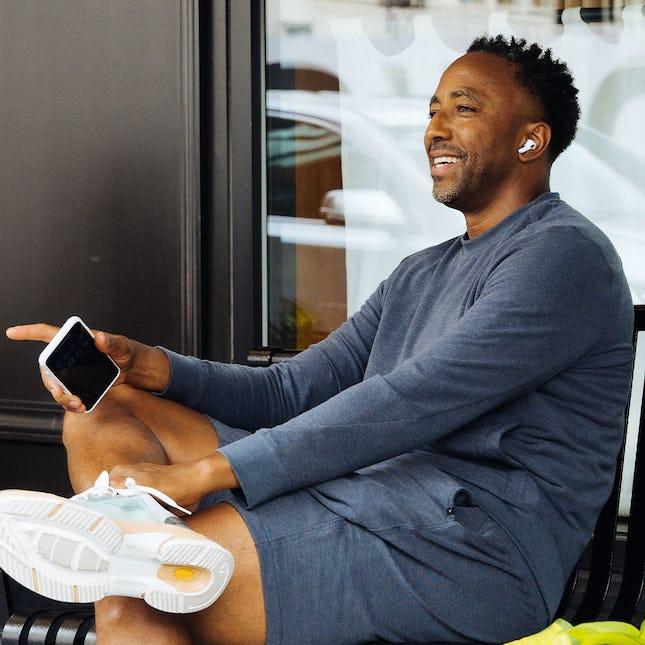 man talking on phone wearing fusion terry shorts and sweatshirt