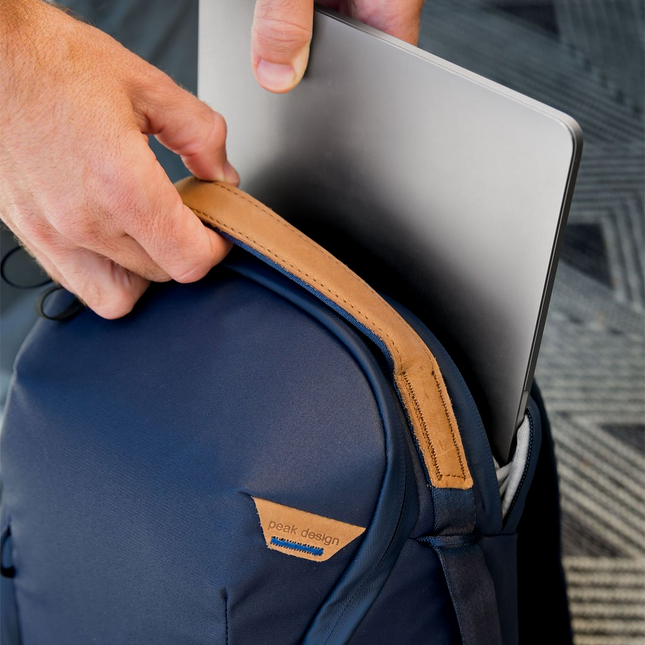 Image of a person putting a silver laptop into a midnight blue backpack