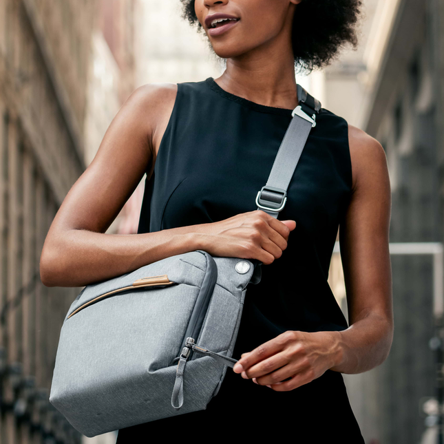 Woman wearing a black tank top and holding a grey crossbody bag standing in a city