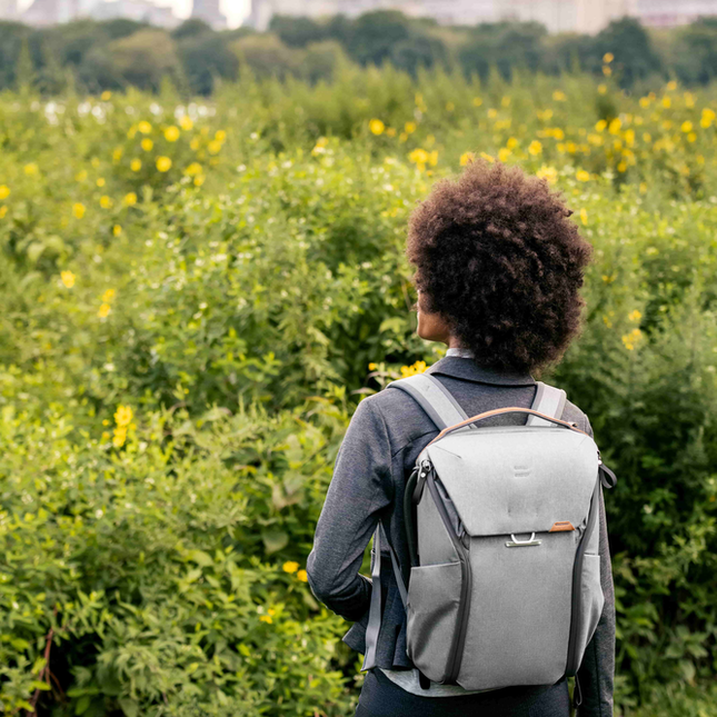 Image of woman wearing a grey backpack looking out at flowers in Central Park