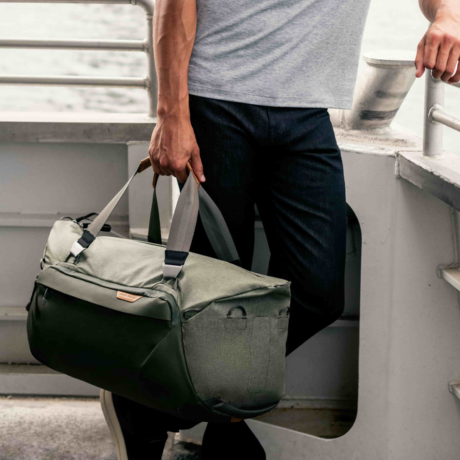 Image of man on a boat holding a green duffel bag