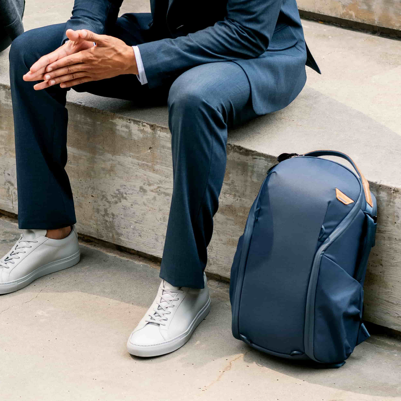 man sitting on a step in a blue suit with a blue backpack next to him