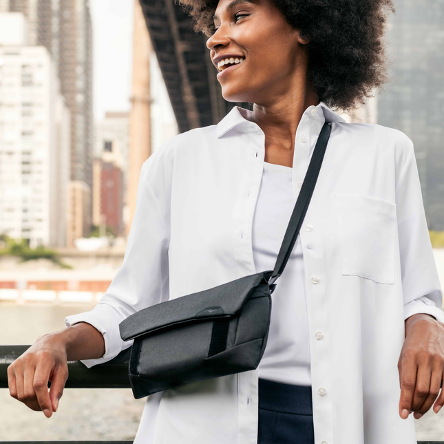 image of a woman leaning against a fence in a white shirt and wearing a small black crossbody bag