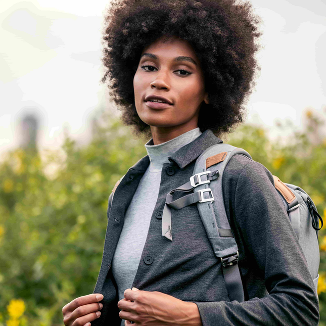 Woman standing in a park wearing a grey shirt and grey backpack