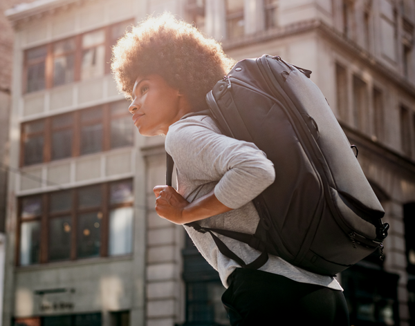 Woman in a city wearing a black backpack and grey shirt