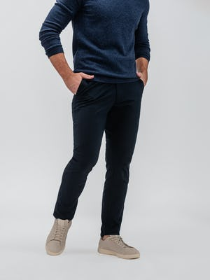 model wearing indigo altas crew neck sweater and navy kinetic tapered pant facing off center with hands in pockets