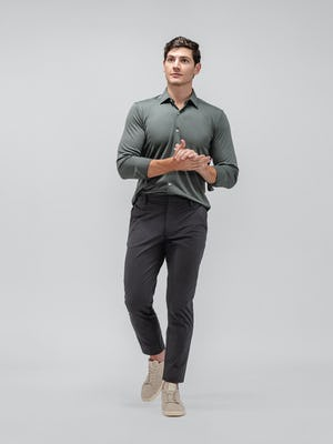 model wearing olive solid apollo shirt and charcoal kinetic tapered pant walking forward with hands clasped