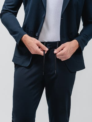 men's navy kinetic tapered pant close up of model adjusting waistband