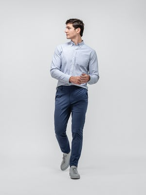 model wearing grey heather houndstooth aero button down and slate blue kinetic tapered pant walking forward with hands clasped