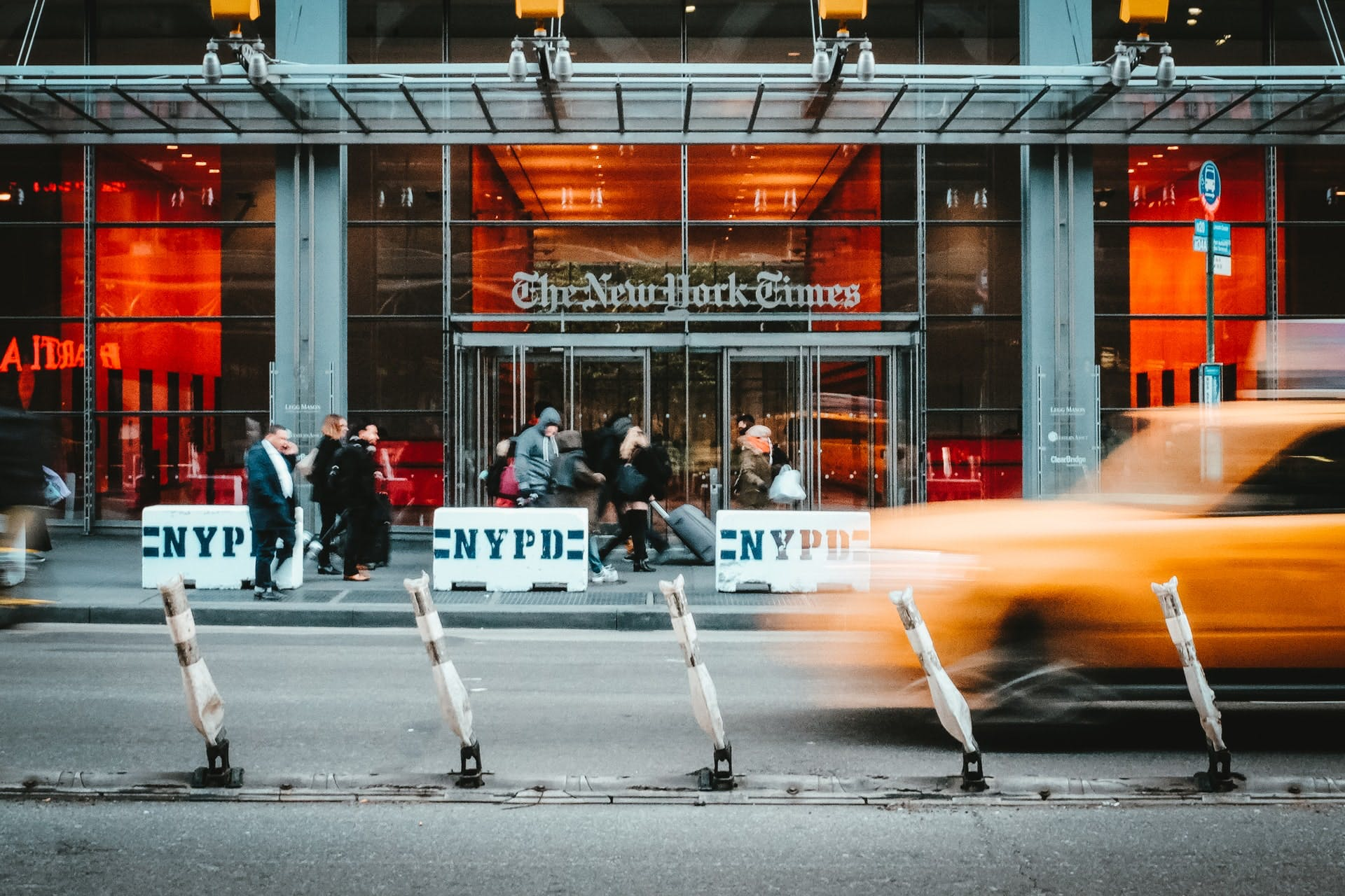 A photo of the New York Times office with a taxi passing in front.