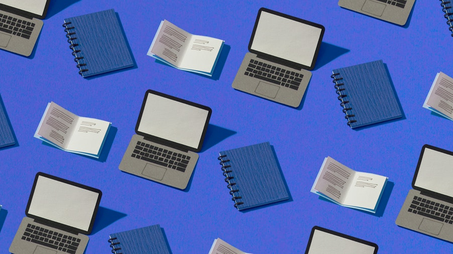 A composite image of paper laptops and binders on a blue background.