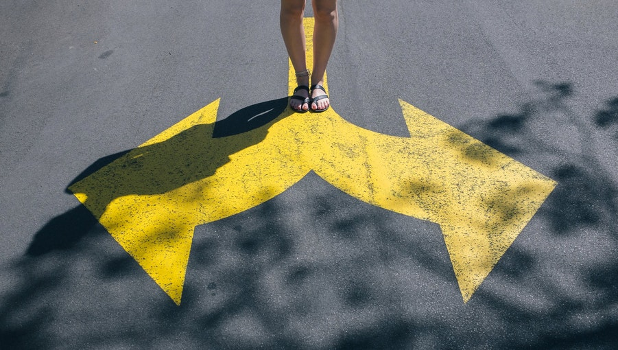 An image of a person standing at a painted crossroads on a road.