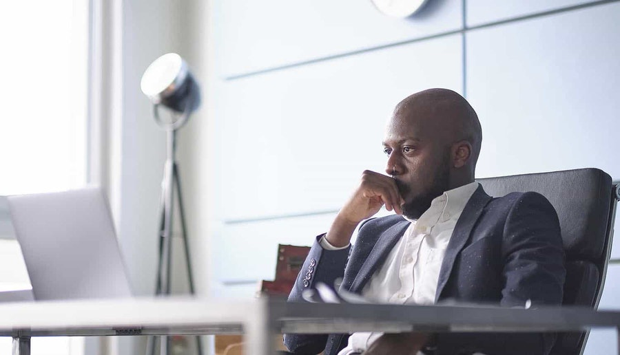 An image of a man sitting at a desk thinking.