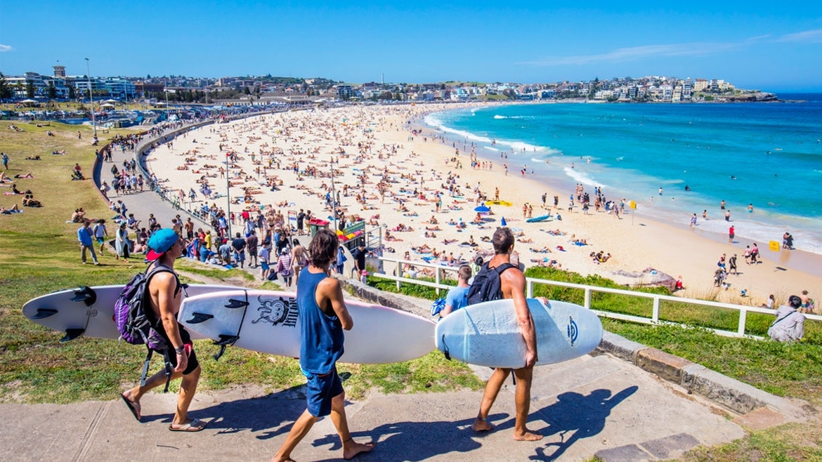 3 surfers walking down the concrete path to the promenade along Bondi Beach, busy with sunbathers on the sand and swimmers in the surf.
