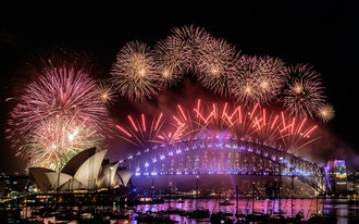 Fireworks explode from the arch of an illuminated Sydney Harbour Bridge with the harbour packed with spectator vessels.