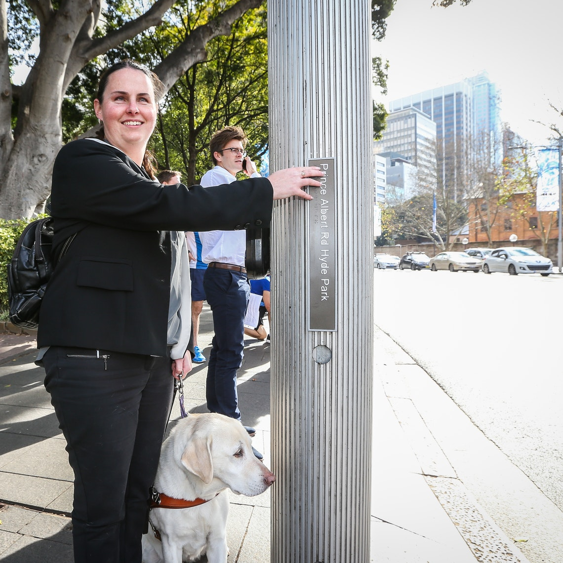A woman with a guide dog uses a tactile street sign at a pedestrian crossing.