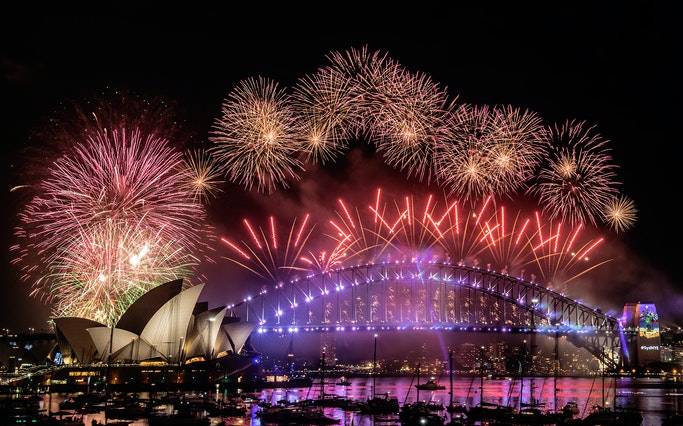 fireworks explode from the arch of an illuminated sydney harbour bridge with the harbour packed with