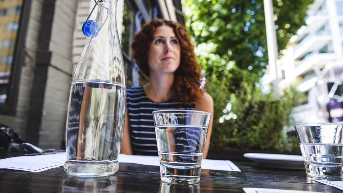 A woman sitting at an outside table with a glass of water