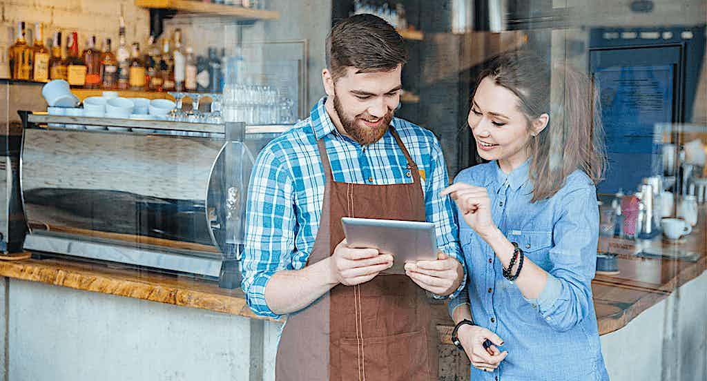 Lokalbesitzer mit Tablet und Kassensystem