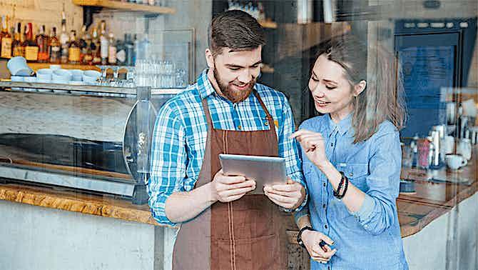 Kellner und Kundin schauen auf ein Tablet Kassensystem