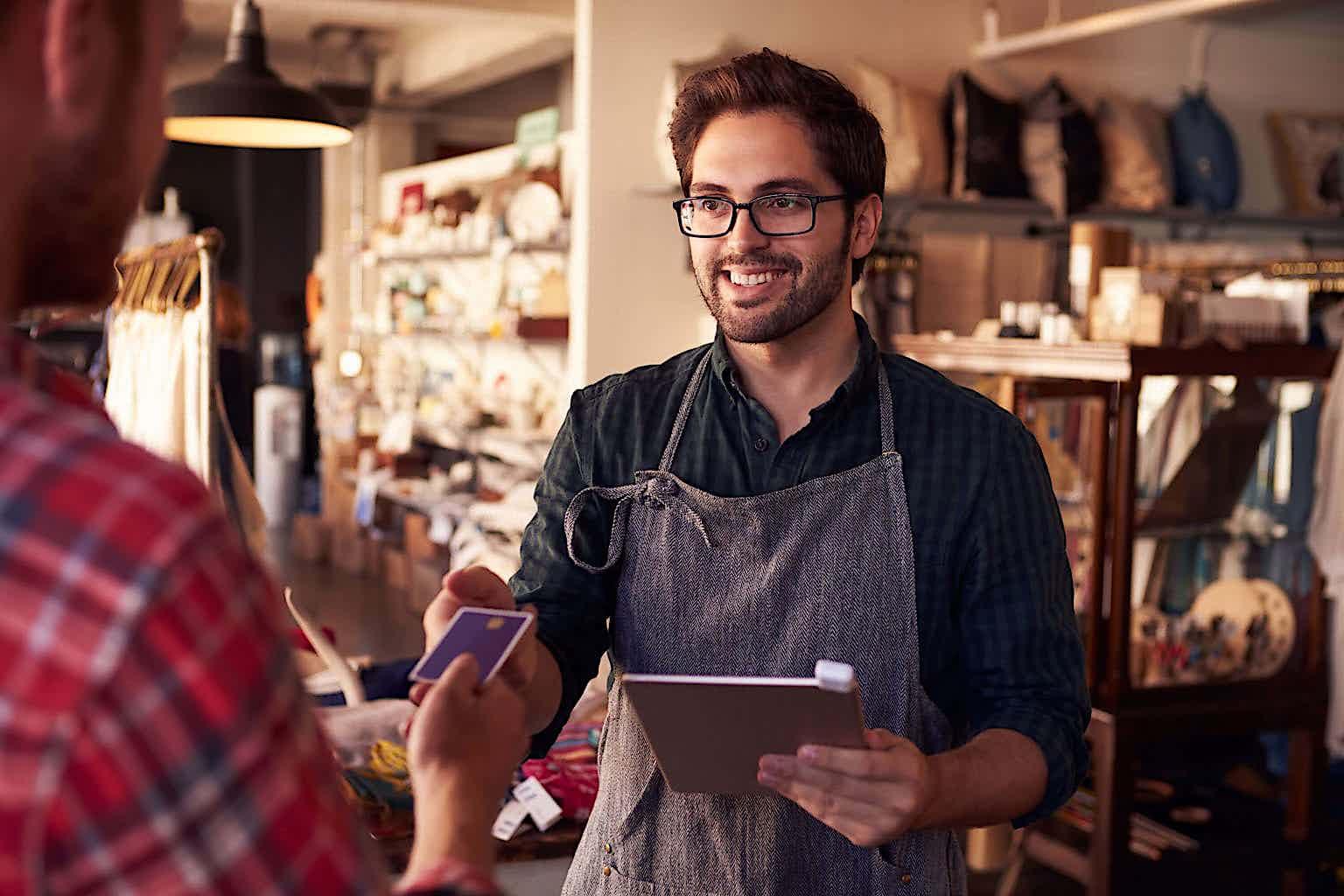 Ein Verkäufer steht hinter seinem Tresen und baut eine Beziehung mit seinem Kunden auf