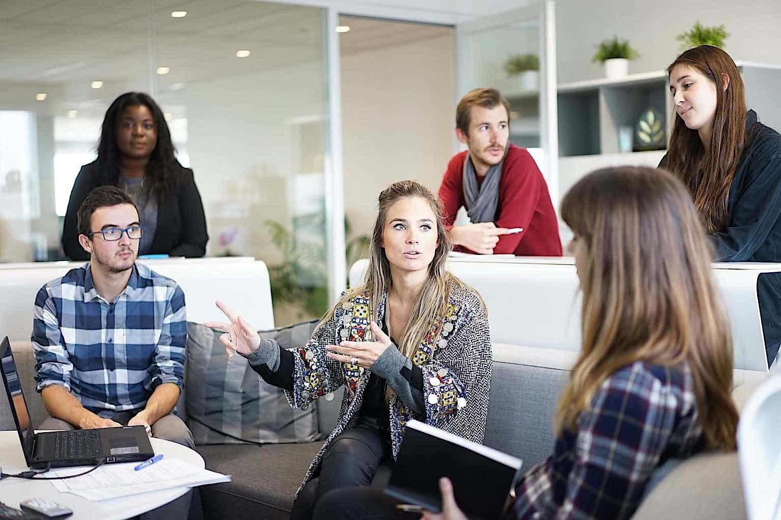 Mehrere Mitarbeiter sitzen im Büro und führen ein Gespräch