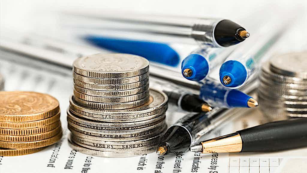 Kleingeld neben Kugelschreibern