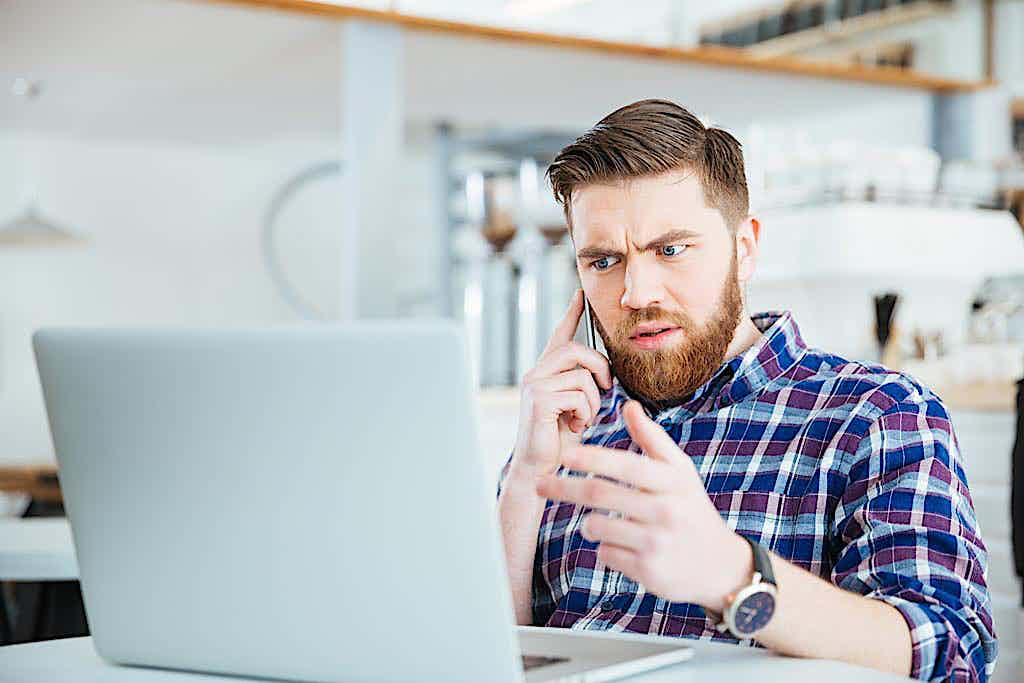 Mann sitzt vorm Laptop und telefoniert