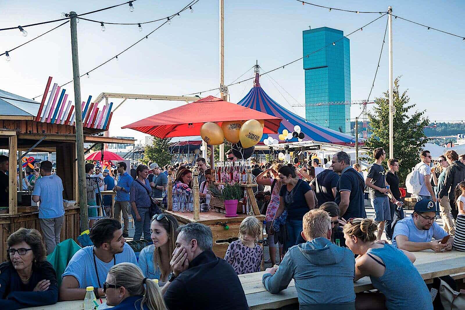 Menschen auf einem street food festival, verschiedene Zelte, im Hintergrund ein Hochhaus