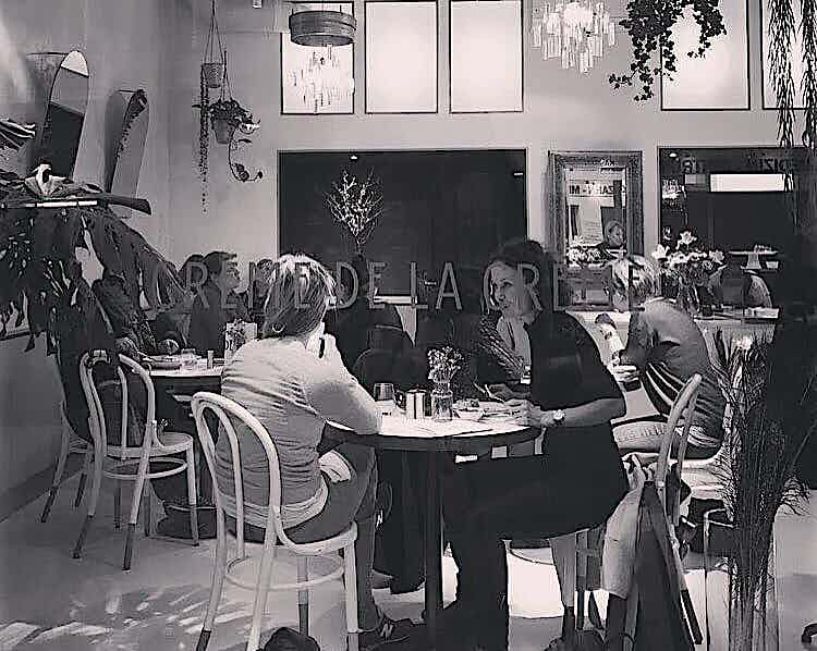 An image that shows people seating in a cafe area