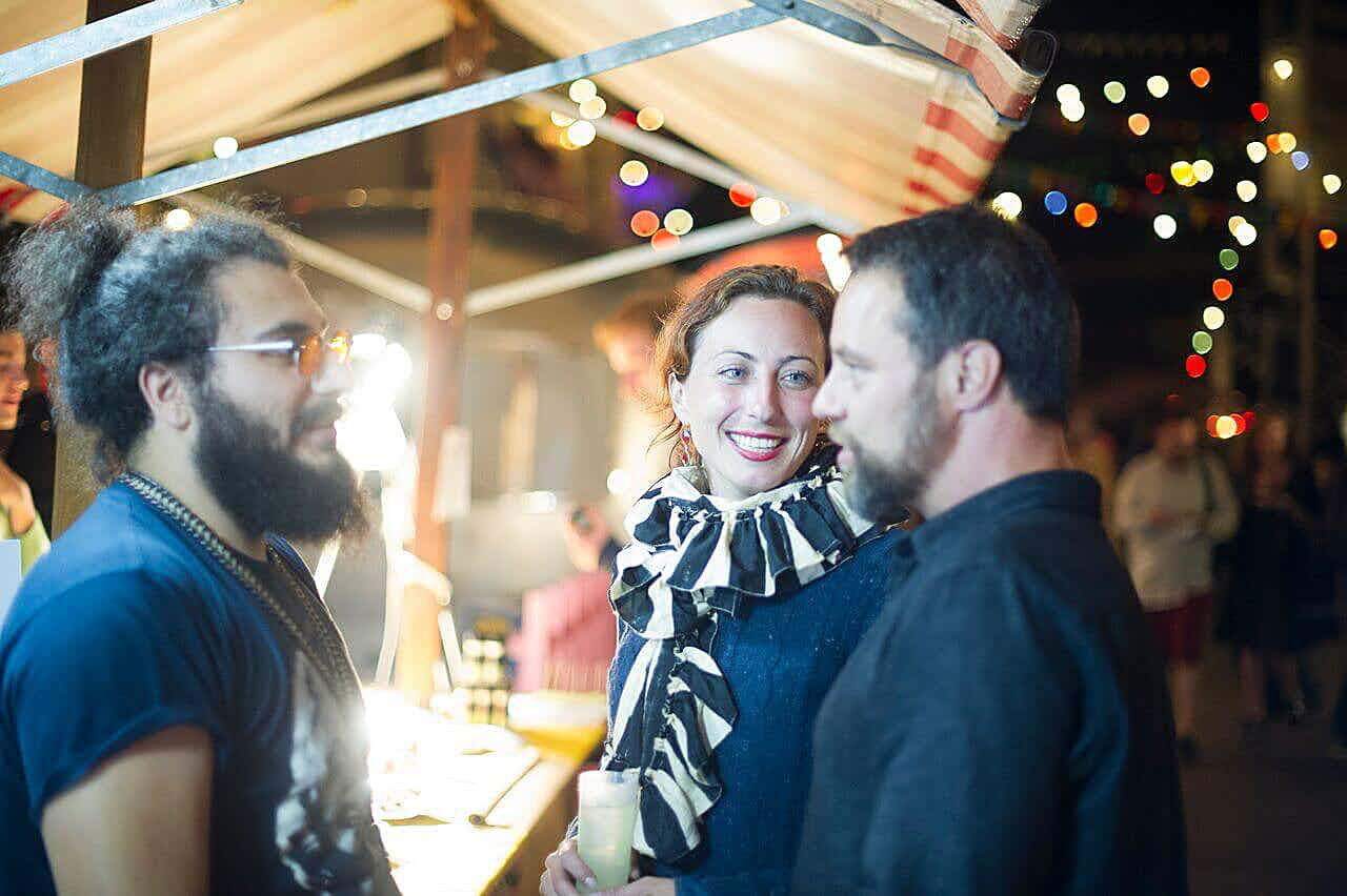 Drei personen unterhalten sich vor einem Stand auf dem street food festival