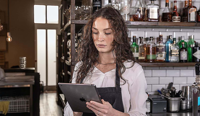 Kellnerin nimmt Bestellung auf iPad auf