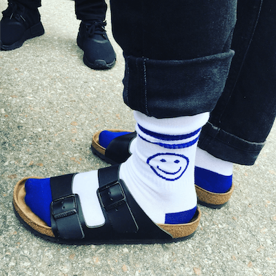 Close-up of someone wearing conference socks with sandals.