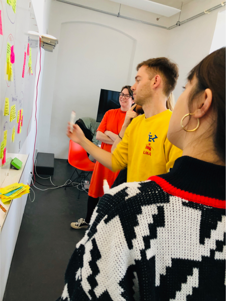 A designer and three developers using post-its on a whiteboard for sprint planning.