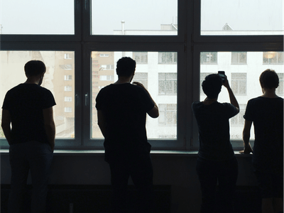 Four people silhouetted against the large office windows, where they are watching and taking photos of snow falling.