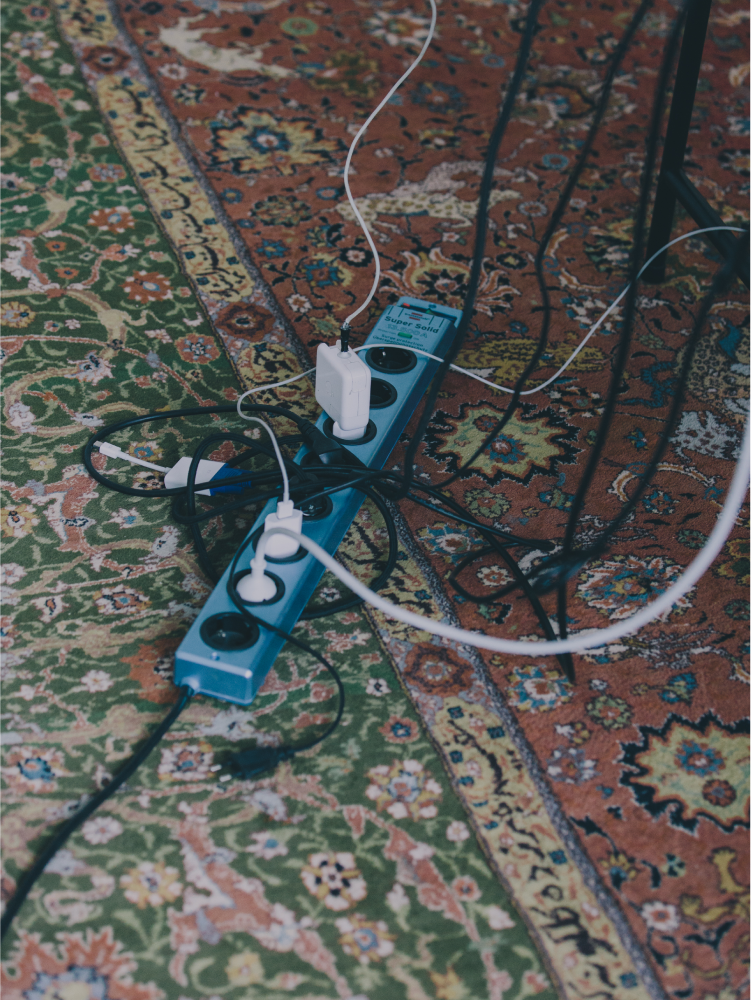 Close-up of an office power strip on a rug, with several laptop chargers and monitor cables plugged into it.